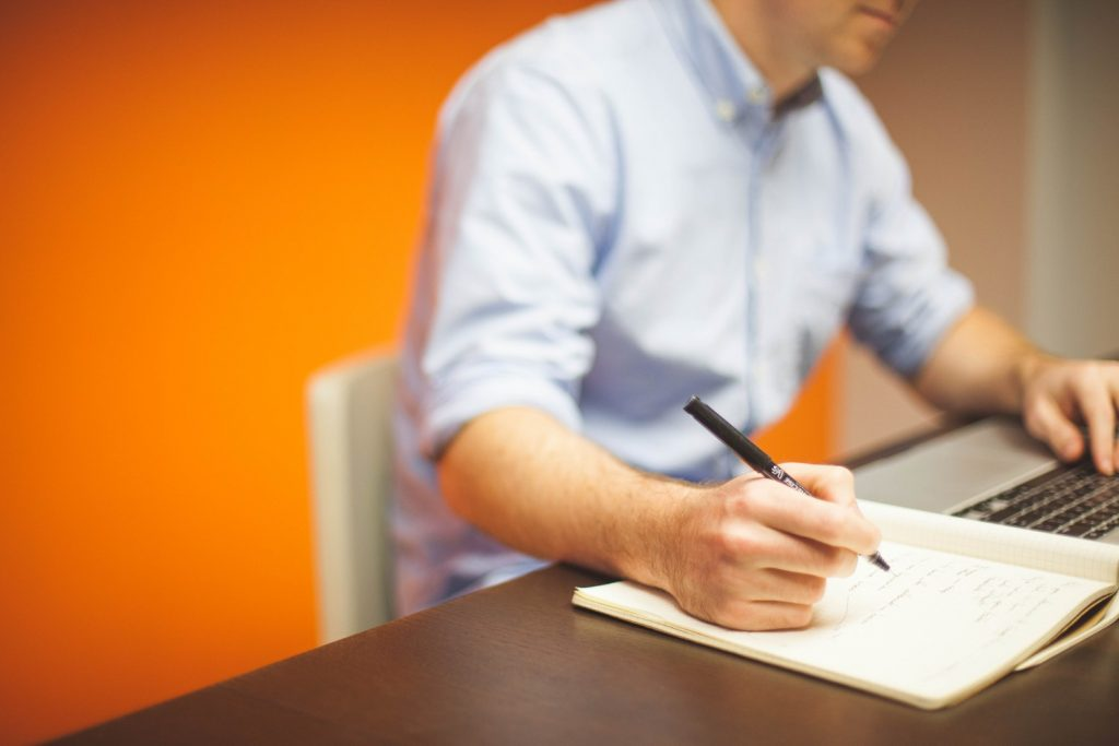 A man behind desk making notes to write work instructions
