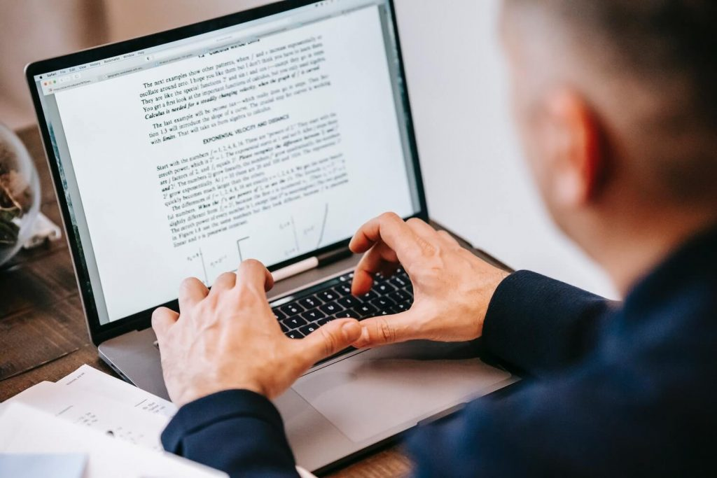 A man writing standard operating procedure (SOPs) on laptop